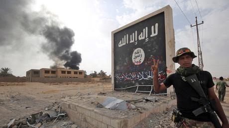 Ein irakischer Kämpfer steht nach dem Kampf gegen den sogenannten Islamischen Staat neben deren Schild. Die USA scheinen es aber nicht so eilig mit der endgültigen Zerschlagung des IS zu haben.