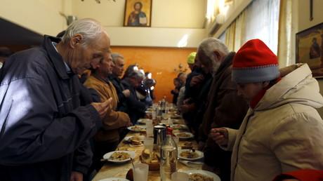 Griechen beten vor dem Essen in einer Suppenküche der Galini-Stiftung der orthodoxen Kirche in Athen