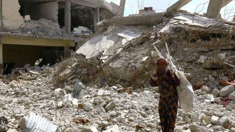 Eine Frau steht auf Trümmern zerstörter Gebäude in Rakka, Syrien, 14. Mai 2018.