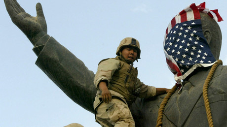 Ein US-Marine bedeckt das Gesicht einer Statue des irakischen Präsidenten Saddam Hussein mit einer US-Flagge. Bagdad, 9. April 2003.