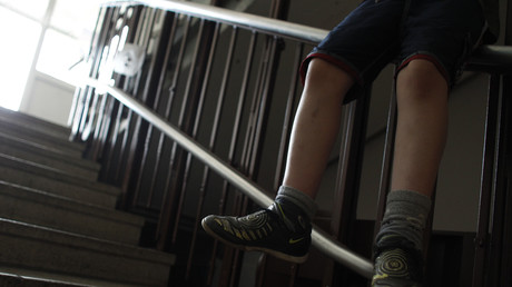 Ein Junge sitzt auf einer Treppe der