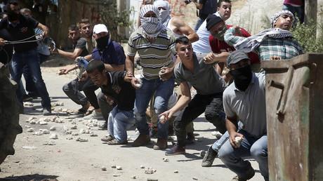 Palästinenser werfen Steine auf israelische Militärs, nachdem eine wöchentliche Demonstration gegen die Enteignung von palästinensischem Land durch Israel im Dorf Kfar Qaddum in der Nähe von Nablus, durch die Streitkräfte mit Gewalt am 24. August 2018 aufgelöst wurde.