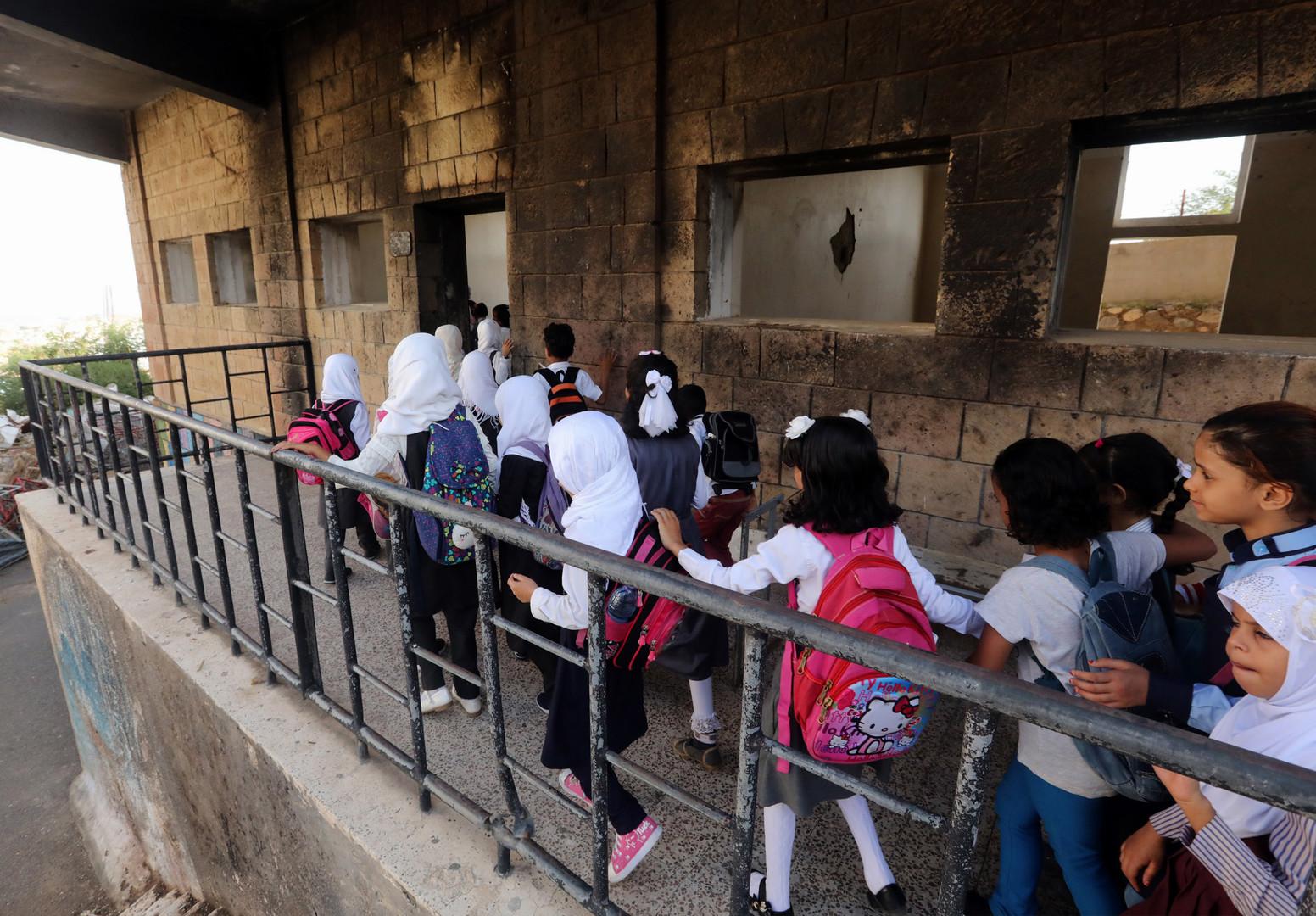 Jemenitische Schüler gehen am ersten Tag des neuen Schuljahres in eine Schule, die im vergangenen Jahr bei einem Luftangriff in der drittgrößten Stadt des Landes, Taez,  beschädigt wurde.