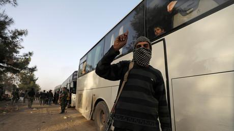 Rebellenkämpfer vor einem Bus mit Ziel Idlib, Damaskus, Syrien, 26. März 2018.