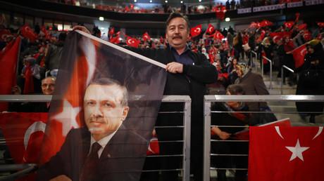 Ein Anhänger des türkischen Präsidenten Erdoğan hält bei einem Auftritt des türkischen Premierministers Binali Yıldırım am 18. Februar 2017 in Oberhausen vor rund 10.000 Menschen eine Fahne hoch. Bei Erdoğans Besuch vom 27. bis 29. September soll es keinen großen Auftritt geben.