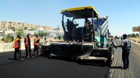 Arbeiter planieren eine Autobahn, die Damaskus mit dem Norden Syriens verbindet. In vielen Teilen des Landes wird am Wiederaufbau der zerstörten Infrastruktur gearbeitet.