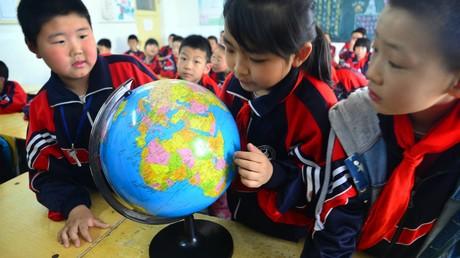 Chinesische Schüler betrachten den Globus. China ist der größte Herausforderer der US-amerikanischen Hegemonie, die Washington unbedingt  aufrechterhalten will.