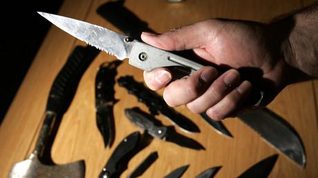 Ein Polizist hält ein Messer über eine Auswahl gefährlicher Waffen, die von der Polizei von Lothian und Borders in der Polizeistation von St. Leonard in Edinburgh, Schottland, beschlagnahmt wurden.