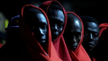 Migranten, die vor der Küste im Mittelmeer abgefangen wurden, warten darauf, das Rettungsboot