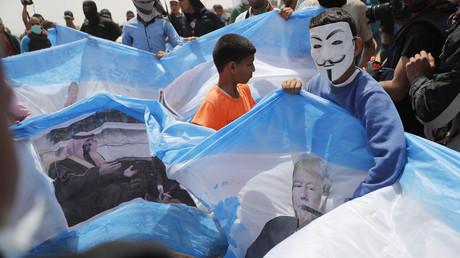 Palästinenser im Gazastreifen protestieren gegen die israelische Blockade und zeigen auf israelischen Flaggen die Porträts von US-Präsident Donald Trump und dem saudischen Kronprinzen Mohammed bin Salman.