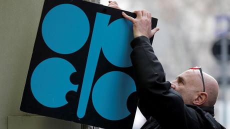 Ein Mann befestigt ein Schild mit dem Logo der OPEC neben dem Hauptsitz der Organisation in Wien.