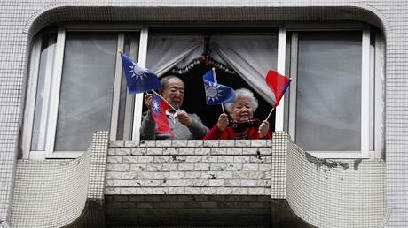 Rentner schwenken auf einem Balkon die Fahnen Taiwans und der Kuomintang.