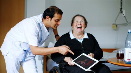 Symbolbild: Ältere Frau mit ihrem jungen, syrischen Pfleger, Düsseldorf, Deutschland, 12. September 2018.