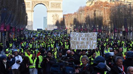 Ein Demonstrant der Gelbwesten-Bewegung hält ein Schild mit der Aufschrift hoch: