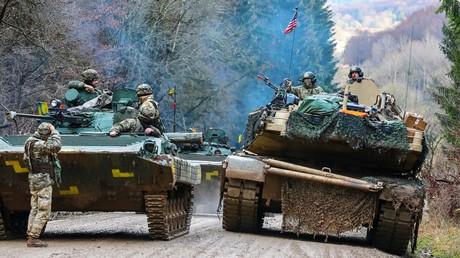Eine Panzerbesatzung der U.S. Army M1A1 Abrams während der Übung Combined Resolve XI an der Seite eine Reihe von gepanzerten Fahrzeugen der ukrainischen Armee, Hohenfels, Deutschland, 10. Dezember 2018.