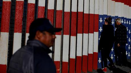 Menschen schauen von Tijuana, Mexiko aus durch den Grenzzaun zu den USA.