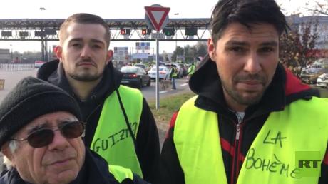 Organisatoren der Gelbwesten in Lyon im Gespräch mit RT Deutsch vor einer Maut-Station, die als