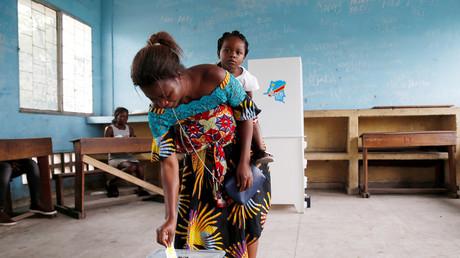 Eine Frau trägt ihr Baby, während sie bei der Präsidentschaftswahl in Kinshasa, Demokratische Republik Kongo, am 30. Dezember 2018 in einem Wahllokal ihre Stimme abgibt.