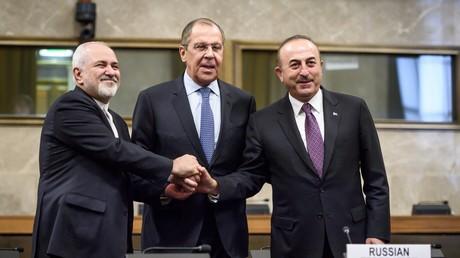 (v. l.) Der iranische Außenminister Mohammad Javad Zarif, der russische Außenminister Sergei Lawrow und der türkische Außenminister Mevlüt Çavuşoğlu schütteln die Hände nach einem Treffen zur Bildung eines Verfassungsausschusses in Syrien am 18. Dezember 2018 in Genf.
