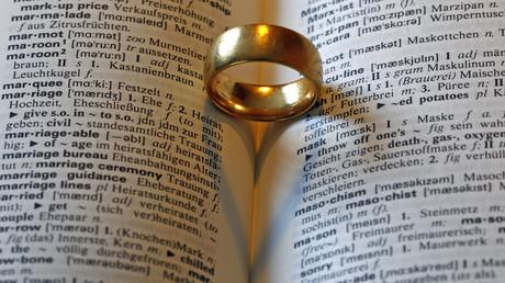 (Symbolbild). Ein Ehering auf einem deutsch-englischen Wörterbuch.