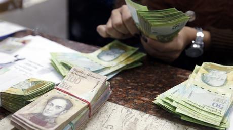 Ein Kassierer zählt Bolivars am Geldwechsel in Caracas, 24, Februar 2015.