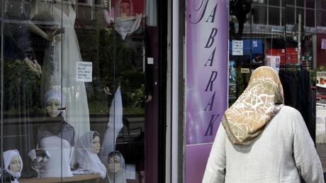 Eine Frau mit Kopftuch geht durch eine Straße im Berliner Stadtteil Neukölln.
