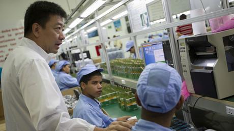 Mitarbeiter von Orinoquia, einer chinesisch-venezolanischen Mobilfunkfabrik, sprechen mit einem chinesischen Instrukteur.