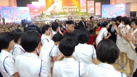 Kim Jong-un (m.), begleitet von seiner Frau Ri Sol-ju (r.), begrüßt die Künstler bei einem Konzert der Moranbong Band im Kulturhaus am 25. April 2014 in Pjöngjang.