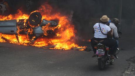 Menschen auf einem Motorrad fahren an einem brennenden Auto vorbei 19b7dca2a89ff