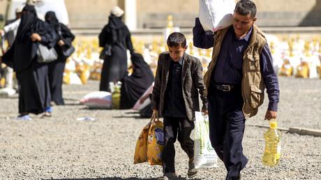 Ein Junge und ein Mann tragen Hilfsgüter, die sie von einer lokalen Hilfsorganisation in der jemenitischen Hauptstadt Sanaa am 14. Februar 2019 erhalten haben.