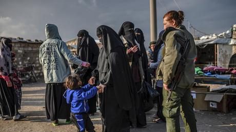 Angebliche Angehörige von IS-Kämpfern unter Bewachung einer SDF-Kämpferin in Nordostsyrien, Februar 2019