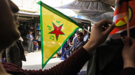 Ein Händler in Syriens Kamischli stellt eine Fahne der kurdischen YPG-Miliz auf.