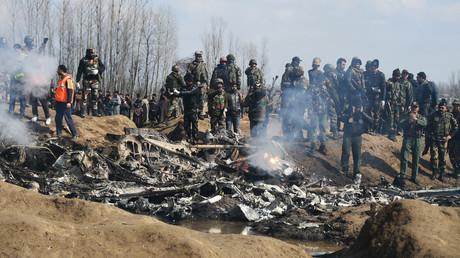 Indische Soldaten und kaschmirische Zuschauer stehen in der Nähe der Überreste eines Flugzeugs der indischen Luftwaffe, nachdem es am 27. Februar 2019 im Bezirk Budgam, am Rande von Srinagar, abgestürzt war.