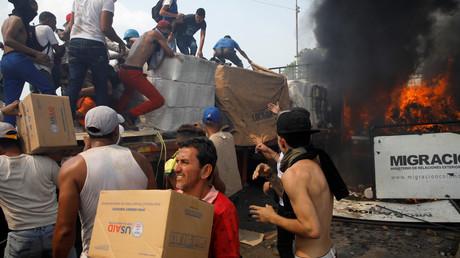 Aktivisten der Opposition entladen USAID-Hilfspakete aus einem brennenden LKW, der wahrscheinlich aus ihren eigenen Reihen heraus angezündet wurde. (23. Februar 2019)