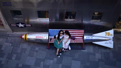 Zwei Frauen sitzen auf einer Bank in Peking, die in Form einer Bombe mit der US-Flagge als Sitzfläche gestaltet ist. Strategisch wichtige US-Munitionsdepots werden zur Zeit mit Offensivwaffen ausgestattet, um sich für den
