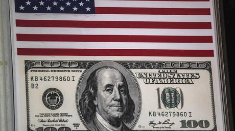 Der US-Dollar, Symbol und Mittel der Macht der Vereinigten Staaten von Amerika, die mit ihrer Politik allerdings immer mehr das US-Dollar-basierte internationale Währungs- und Finanzsystem untergraben – und damit die Grundlage ihrer eigenen globalen Vorherrschaft.