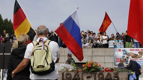 (Symbolbild: Ein Pärchen mit Russland- und Deutschlandfahne am Sowjet-Kriegsdenkmal im Treptower Park in Berlin)