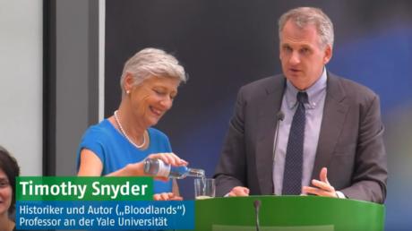 Snyder im Juni 2017, zu Gast bei den Grünen. Marieluise Beck reicht ihm das Wasser. Titel der Veranstaltung: