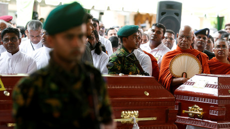 Sicherheitskräfte und Mönche stehen am 23. April 2019 während einer Messe in Negombo, Sri Lanka, in der Nähe der Särge der Opfer.
