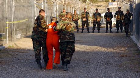 US-Militärpolizisten eskortieren einen Häftling im Straflager Guantánamo.