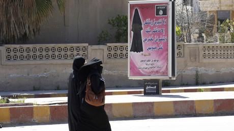 Symbolbild: Verhüllte Frauen passieren ein Schild der Terrororganisation IS mit dem Gebot, sich zu verschleiern, Rakka, Syrien.