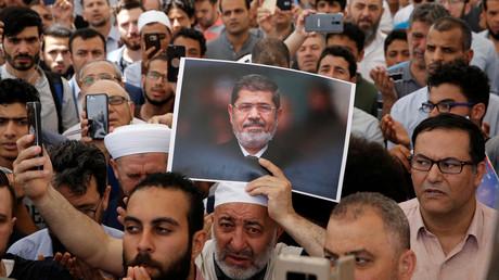 Ein Mann hält ein Bild des ehemaligen ägyptischen Präsidenten Mohamed Mursi während eines symbolischen Trauergebets im Innenhof der Fatih-Moschee in Istanbul, Türkei, am 18. Juni 2019.
