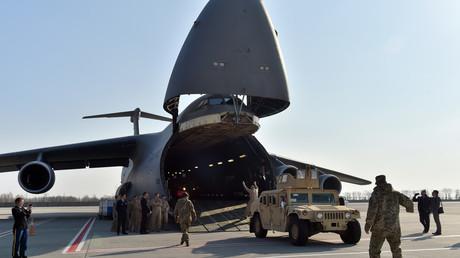 Ukrainische und US-amerikanische Soldaten entladen am 25. März 2015 gepanzerte Fahrzeuge aus einem Flugzeug am Flughafen Kiew. Nun kündigte Pentagon an, der Ukraine weitere militärische Unterstützung zur Verfügung zu stellen.