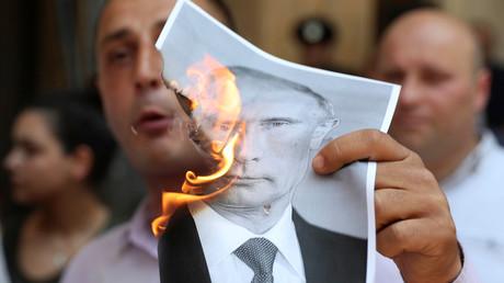 Ein Protestler verbrennt am 20. Juni 2019 in der georgischen Hauptstadt Tiflis ein Bild des russischen Präsidenten.