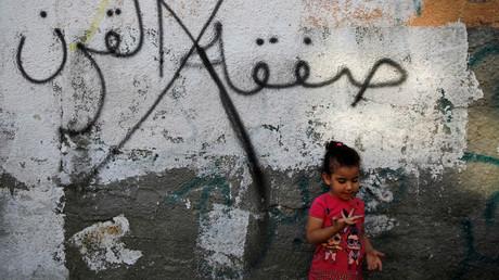 Ein palästinensisches Mädchen vor einem Graffiti mit Bezug auf die von Washington veranstaltete Konferenz