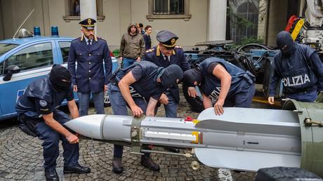 Vermummte Polizisten sichern die Luft-Luft-Rakete.