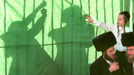 Symbolbild: Ein Junge berührt bei einer Hochzeit die Schatten der orthodoxen Mädchen hinter einem verdeckten Zaun, Jerusalem, Israel, 1.12.1998.