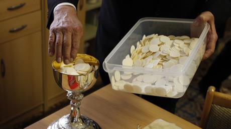 Ein katholischer Sakristan platziert Hostien in einem Kelch als Vorbereitung auf einen Gottesdienst, Dresden, 1. April 2010.