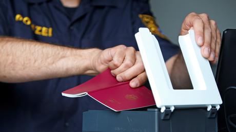 Ein bayerischer Polizist kontrolliert einen Pass am Grenzübergang Kirchdorf am Inn, Deutschland, 18. Juli 2018.