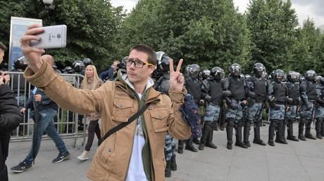 Ein Protestler macht Selfie am 3. August in Moskau vor einer Polizeiabsperrung